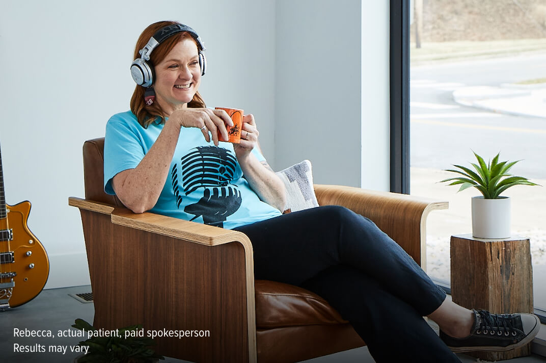 Rebecca relaxing in a chair while drinking coffee and listening to music on headphones